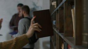 Żeńska ręka podnosi up książkę od półki w bibliotece zbiory