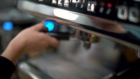 Żeńska ręka przymocowywa właściciela z kawą w fachowej kawowej maszynie gotowej robić kawie lub kawie espresso z bliska zbiory