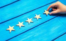 Żeńska ręka stawia kwinty drewnianą gwiazdę na błękitnym tle Krytyk ustawia ilości ocenę Pięć gwiazd wysoka ilość Fotografia Royalty Free