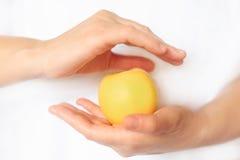 Żeńska ręka trzyma Apple na białym tle Obrazy Royalty Free