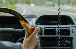 Żeńska ręka trzyma babeczkę za kołem samochód w ruchu na autostradzie zdjęcia royalty free