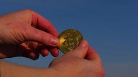 Żeńska ręka trzyma bitcoin monetę w rękach przeciw niebieskiemu niebu zbiory wideo