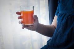 Żeńska ręka trzyma filiżankę sok pomarańczowy w ranku gdy ona wak obrazy stock