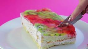 Żeńska ręka trzyma nóż i ciie owoc tort w kawałki zbiory