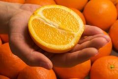 Żeńska ręka trzyma połówkę pomarańcze Zdjęcie Royalty Free