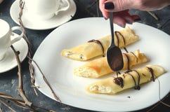 Żeńska ręka trzyma spoonful czekolada i kropi trzy rolki na białym talerzu Horyzontalna orientacja Fotografia Stock
