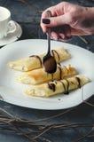 Żeńska ręka trzyma spoonful czekolada i kropi trzy rolki na białym talerzu Pionowo orientacja Obraz Royalty Free