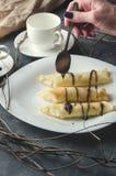 Żeńska ręka trzyma spoonful czekolada i kropi trzy rolki na białym talerzu Pionowo orientacja Zdjęcia Stock