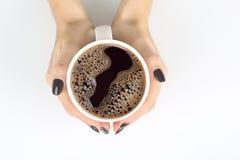 Żeńska ręka z filiżanką czarna kawa na białym stołowym wierzchołku Fotografia Stock