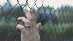 Żeńska ręka z pierścionkiem i błękitna manicure'u macania ogrodzenia siatka chodzimy na ulicie zbiory