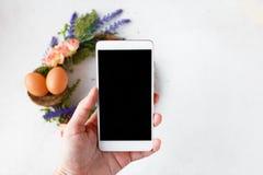 Żeńska ręka z telefonem bierze obrazki Wielkanocny wianek z jaskrawymi wiosna kwiatami, gniazdeczko z Wielkanocnymi jajkami fotografia royalty free