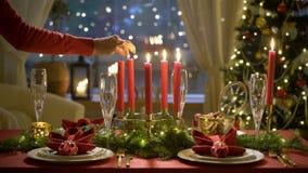 Żeńska ręka zaświeca boże narodzenie świeczki Świąteczny czerwień stołu położenie z girlandą zbiory