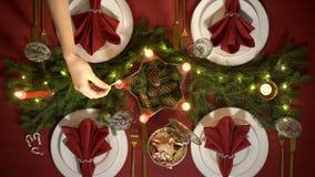 Żeńska ręka zaświeca boże narodzenie świeczki Świąteczny czerwień stołu położenie z girlandą zbiory wideo