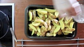 Żeńska ręki dostawiania sól i pikantność nieociosani kartoflani kawałki w smażyć nieckę lub wypiekowego prześcieradło zdjęcie wideo
