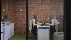Żeńska sekretarka pracuje w wygodnym odbiorczym biurze z ściana z cegieł i szklanym drzwi zbiory wideo