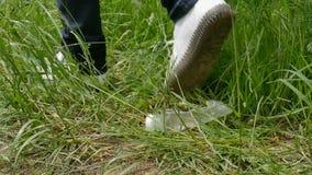 Żeńska stopa w biel butów kroku na plastikowym bidonie w zielonej trawie w parku lub lesie Oprócz środowiska i zdjęcie wideo