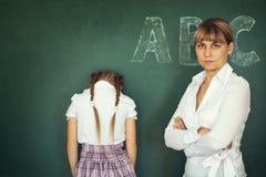 Żeńska techer kara jej dziewczyna uczeń nad chalkboard fotografia stock