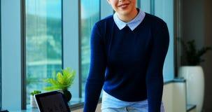 Żeńska wykonawcza pozycja przy jej biurkiem w biurze zdjęcie wideo