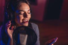 Żeński śpiew śpiewający z telefonem komórkowym przy studiiem nagrań Obrazy Stock