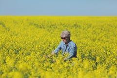Żeński agronom egzamininuje kwitnący rapeseed pole Zdjęcia Stock