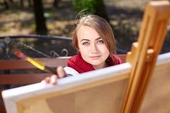 Żeński artysta maluje obrazek w jesień parku fotografia stock