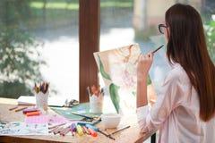 Żeński artysta patrzeje obrazek kwiat zdjęcia royalty free
