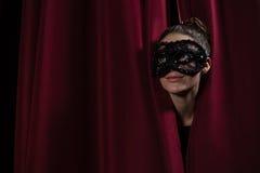 Żeński artysta w maskowym zerkaniu przez czerwonej zasłony Fotografia Stock