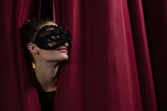 Żeński artysta w maskowym zerkaniu przez czerwonej zasłony Obrazy Royalty Free