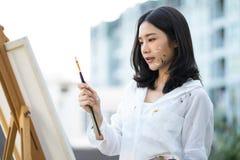 Żeński artysty malarz patrzeje paintbrush przy kanwą w ho Obraz Stock