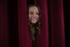 Żeński artysty zerkanie przez czerwonej zasłony Fotografia Royalty Free