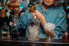 Żeński barman nalewa pomiarowego szkła filiżanka z kostka lodu żółtego alkoholicznego napój od stalowej osadzarki zdjęcia royalty free