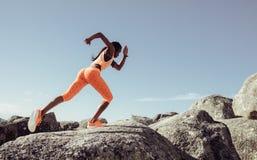 Żeński biegacz biega nad dużymi skałami fotografia stock