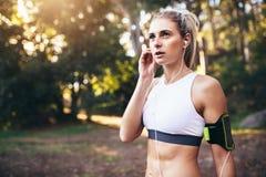 Żeński biegacz jest ubranym słuchawki podczas treningu fotografia stock