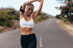 Żeński biegacz relaksuje jej mięśnie zdjęcia royalty free