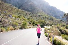 Żeński biegacz z halnym tłem fotografia royalty free