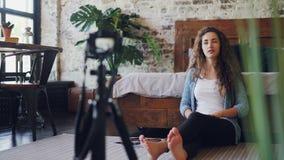 Żeński blogger jest opowiadający i gestykulujący wtedy machający rękę jej zwolennicy nagrywa wideo dla onlinego vlog w domu wewną zdjęcie wideo