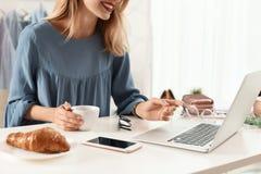 Żeński blogger z laptopem i filiżanka kawy przy stołem indoors obraz stock