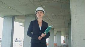 Żeński budowa kierownik przedstawia projekt patrzeje kamerę z projektem na placu budowy Obraz Stock