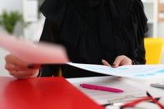 Żeński chwyt w ręka papierach siedzi przy stołem fotografia stock