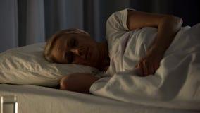 Żeński cierpliwy dosypianie w łóżku szpitalnym, problem zdrowotny, przechodzić na emeryturę pełnoletniego kalectwo fotografia stock