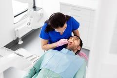Żeński dentysta sprawdza w górę męskich cierpliwych zębów zdjęcia royalty free