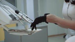 Żeński dentysta stawia dalej medyczne rękawiczki przy krzesłem zbiory