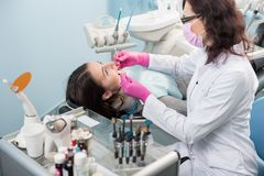 Żeński dentysta z stomatologicznymi narzędziami - odzwierciedla częstowanie cierpliwych zęby i bada sondą przy stomatologicznym k obraz royalty free