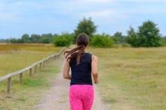 Żeński dorosły jogger bieg zdala od kamery obraz royalty free