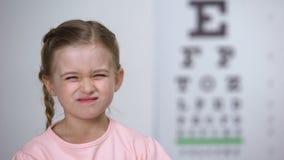 Żeński dziecko z biednym wzrokiem szczęśliwym być ubranym wygodnych eyeglasses, uśmiech zbiory