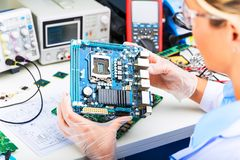 Żeński elektroniczny inżynier egzamininuje komputerową płytę główną w lab obraz royalty free