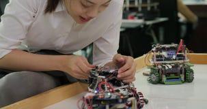 Żeński elektronika inżynier pracuje z robotem, budynek, naprawianie robotyka w warsztacie zdjęcie wideo