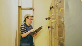 Żeński elektryczny inżynier nagrywa czytania elektryczni urządzenia w switchboard zdjęcie wideo