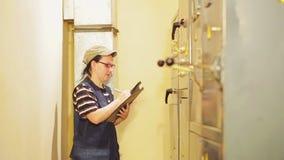 Żeński elektryczny inżynier nagrywa czytania elektryczni urządzenia w switchboard zbiory wideo
