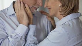 Żeński emeryt cupping męskiego policzek, mężczyzna całuje jej rękę, harmonijny życie rodzinne zbiory